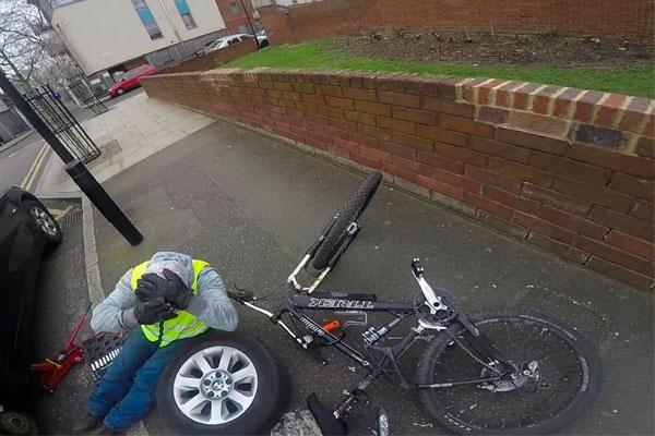Un ciclista torpe por la acera y un conductor reparando el coche en plena calle: una mala (aunque divertida) combinación