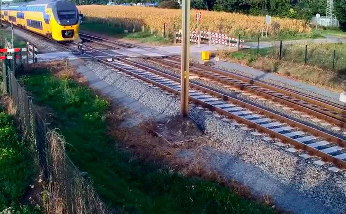 Ciclista imprudente a punto de ser arrollado por un tren en un paso a nivel con las barreras bajadas